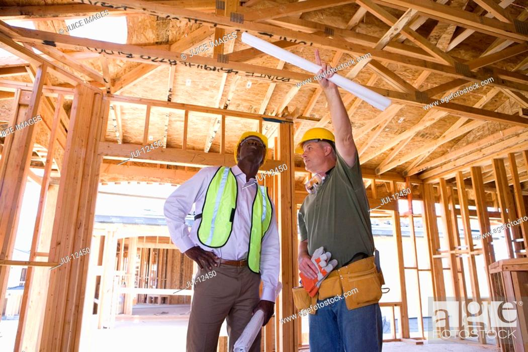 Stock Photo: Builder in hardhat pointing up to businessman in partially built house, low angle view.