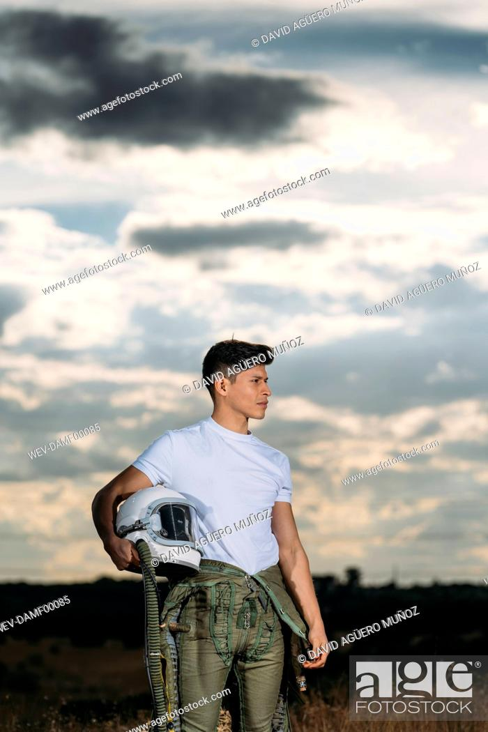 Stock Photo: Man posing dressed as an astronaut on a meadow with dramatic clouds in the background.