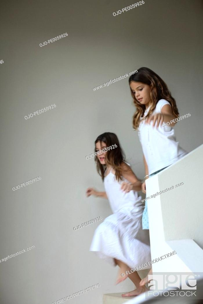 Stock Photo: Two young girls in corridor by staircase.