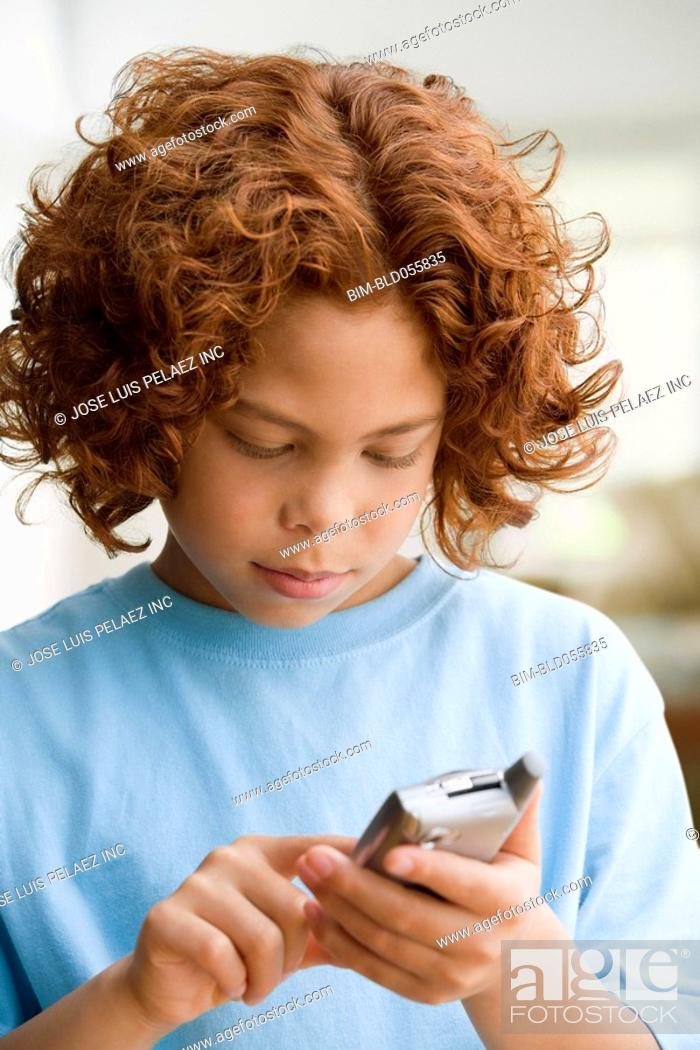 Stock Photo: Mixed Race boy dialing cell phone.