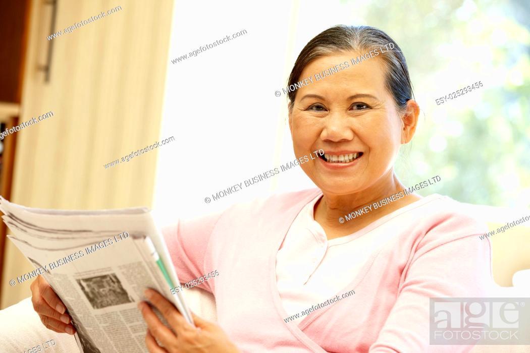 Stock Photo: Senior Asian woman reading newspaper.