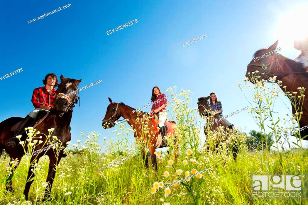 Stock Photo: Portrait of happy equestrians riding bay horses in the flowery meadow at sunny day.