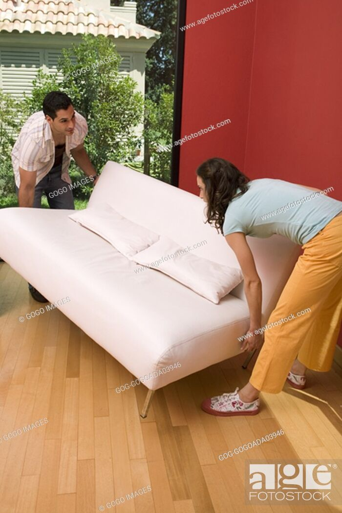 Stock Photo: Couple setting couch down gently.