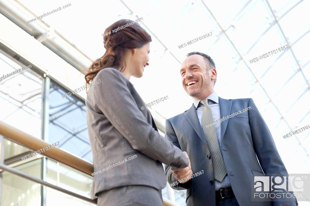 Stock Photo: Germany, Leipzig, Business people shaking hands, smiling.