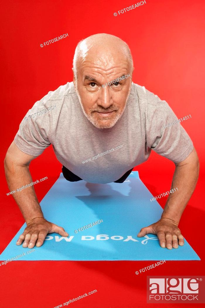 Stock Photo: Senior man doing push ups.