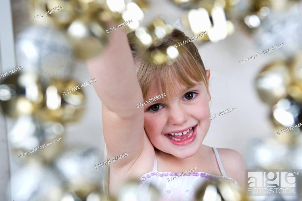 Stock Photo: Young girl in a party dress, holding a Christmas decoration.