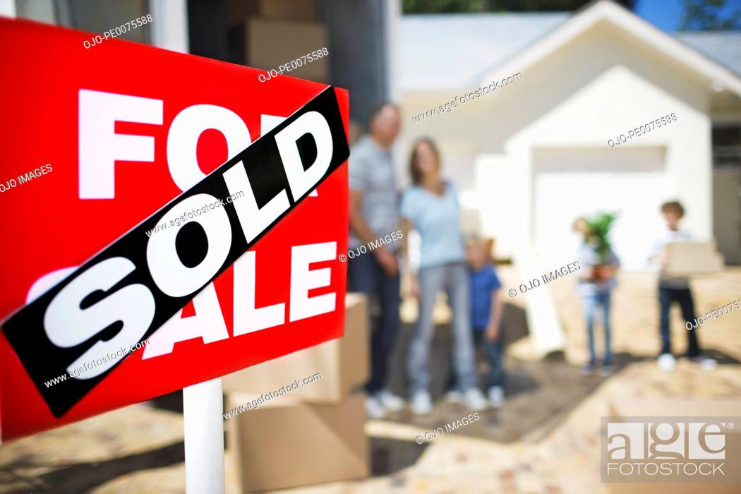Stock Photo: Sold sign on house with family in the background.