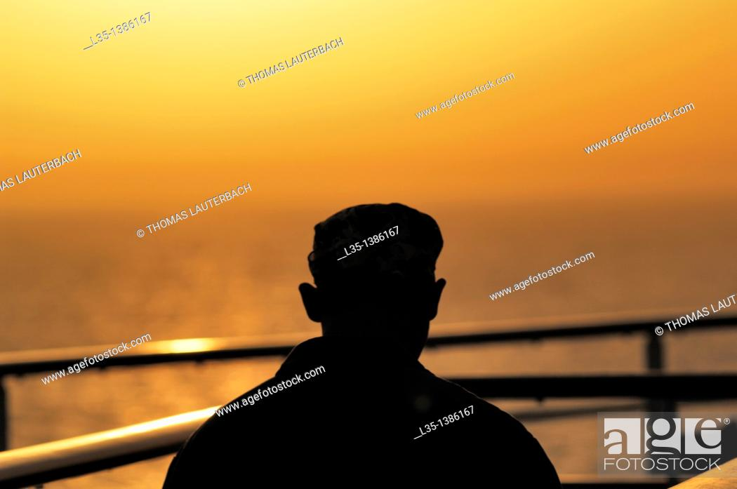 Stock Photo: A man looks at hazy sunset over the Mediterranean.