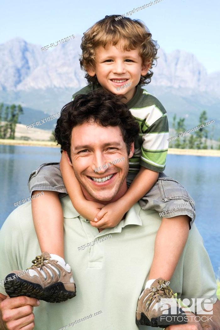 Stock Photo: Father carrying son 4-7 on his shoulders, outdoors, lake in background.