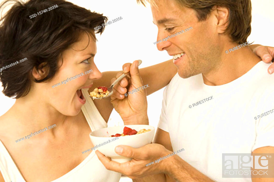 Stock Photo: Close-up of a young man feeding a young woman.