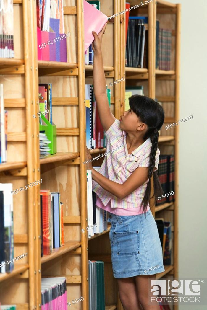 Stock Photo: Schoolgirl 10-13 in library stretching to put book in bookshelf.