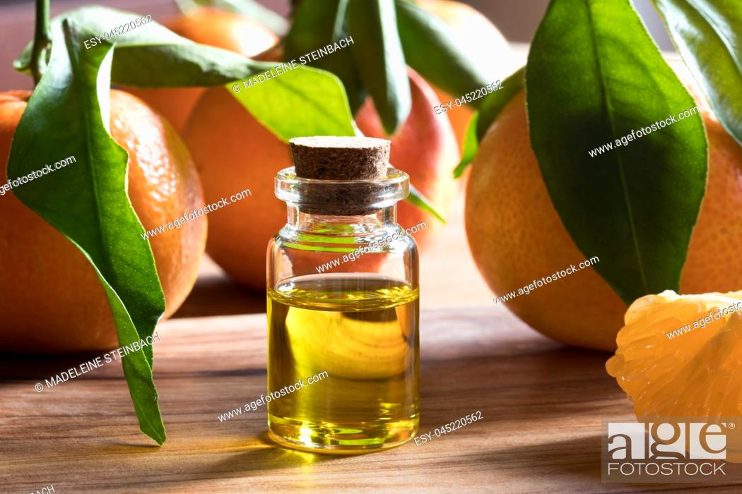 Stock Photo: A bottle of tangerine essential oil on a wooden table, with fresh tangerines in the background.
