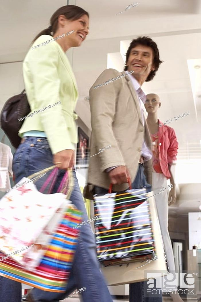 Stock Photo: Couple with shopping bags walking past window display in shop, low angle view blurred motion.