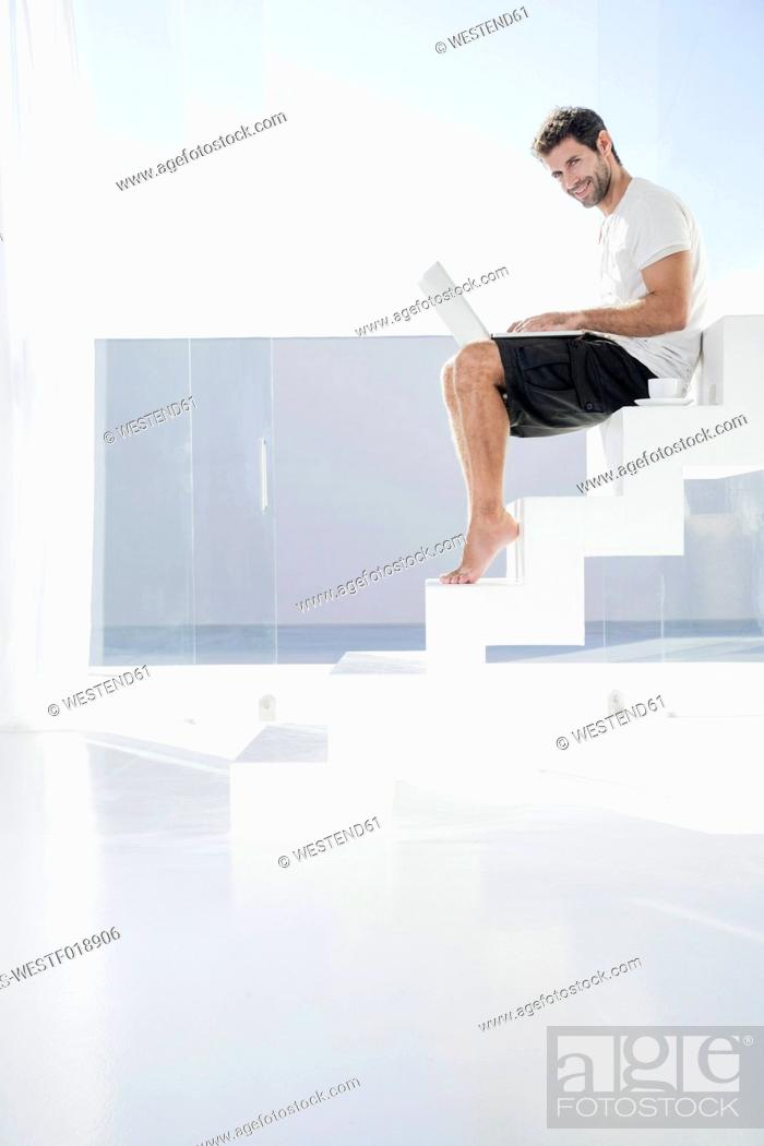 Stock Photo: Spain, Mid adult man sitting on stairway with laptop.
