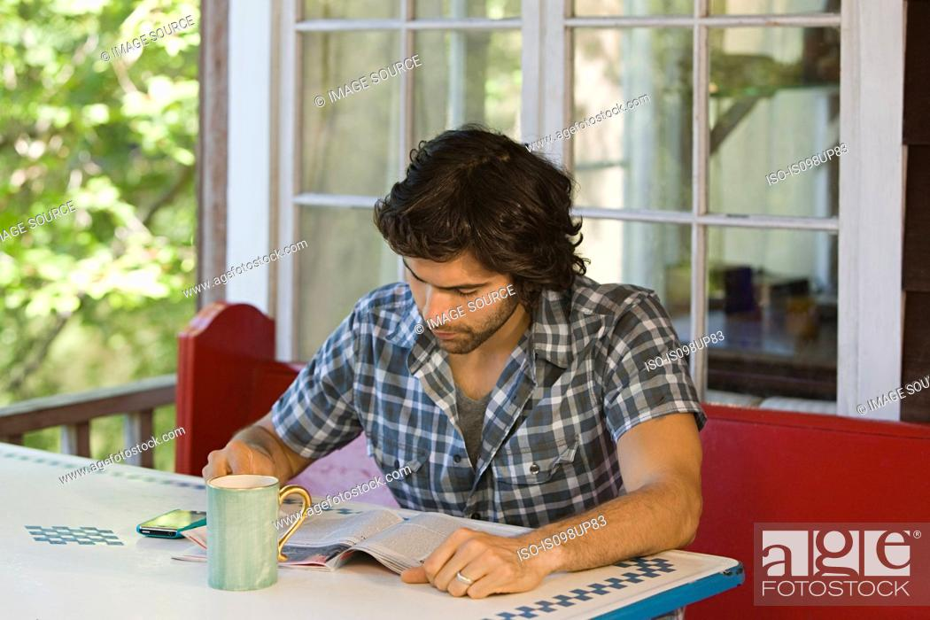 Stock Photo: Young man reading magazine.