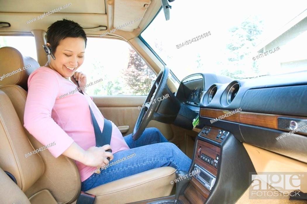 Stock Photo: Pregnant woman putting on seatbelt in car.