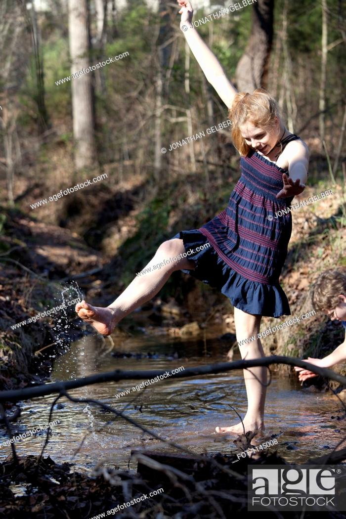 Stock Photo: Girl kicking her feet through the water in Mooresville, North Carolina, USA.