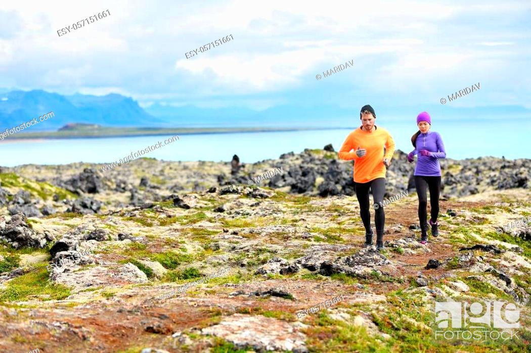 Imagen: Exercise running sport. Runners on cross country trail run outdoors working out. Fit young fitness model man and asian woman training together outside in.