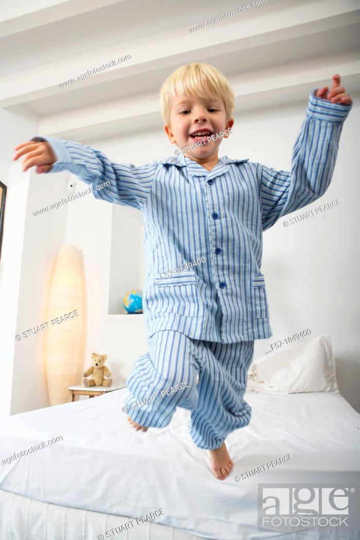 Stock Photo: Four year old boy jumping off the bed.
