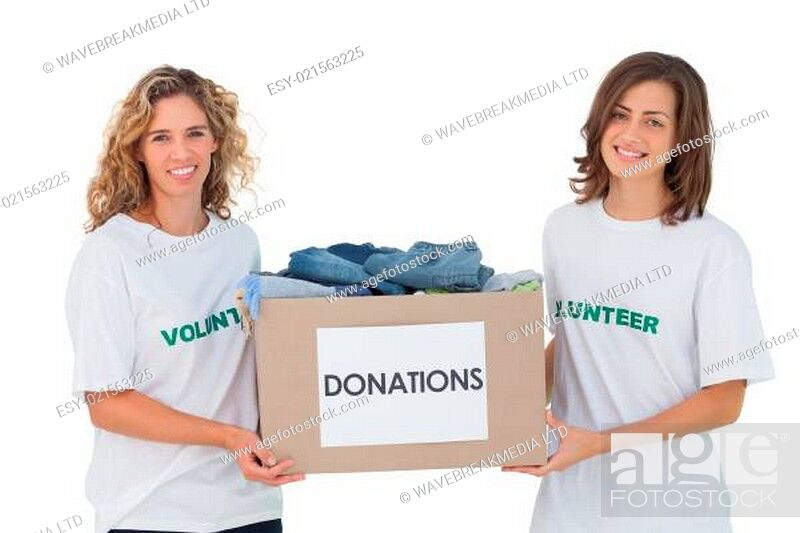 Stock Photo: Two cheerful volunteers carrying clothes donation box.