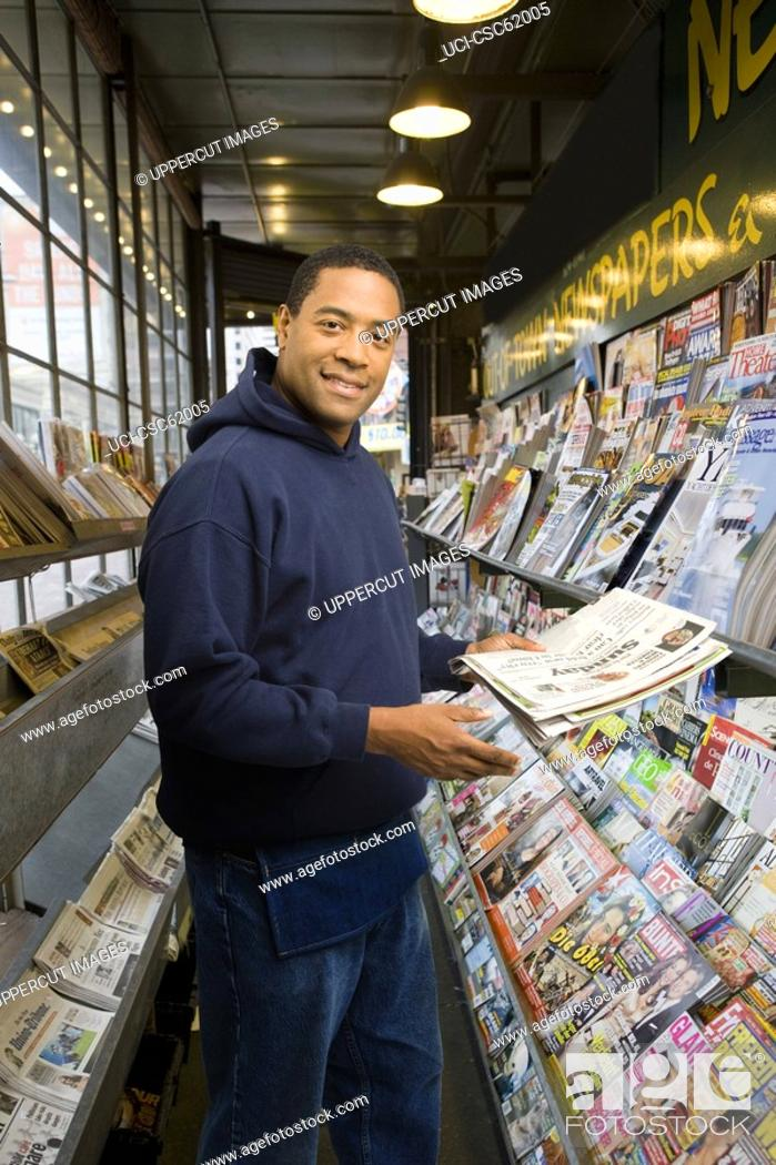 Stock Photo: Man at newspaper stand.