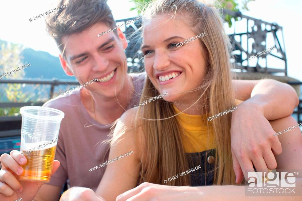 Stock Photo: Young couple with drinks at roof terrace party.