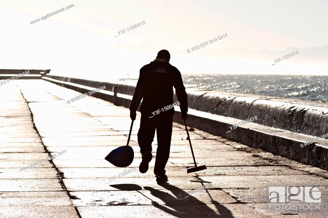Stock Photo: A cleaner walks along the harbour wall, slowly sweeping up rubbish left by fishermen the day before.