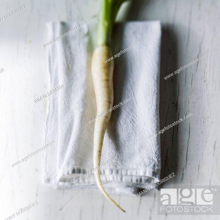Stock Photo: White carrot on napkin on white wooden table.