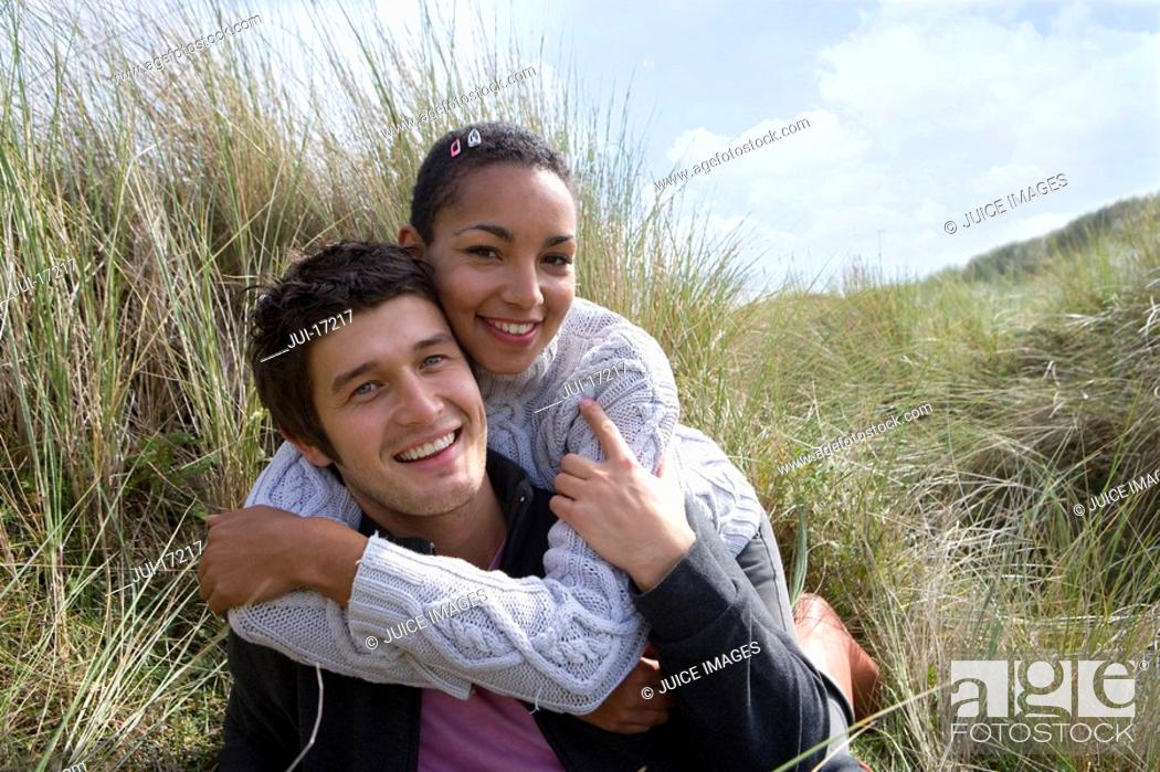Stock Photo: Portrait of mixed race couple in grass.