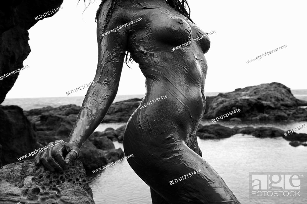 Stock Photo: Young adult Caucasian female nude covered in mud on coastline.