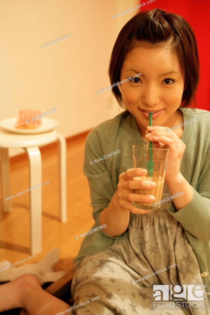 Stock Photo: A young woman takes a sip from a glass as she smiles at the camera.
