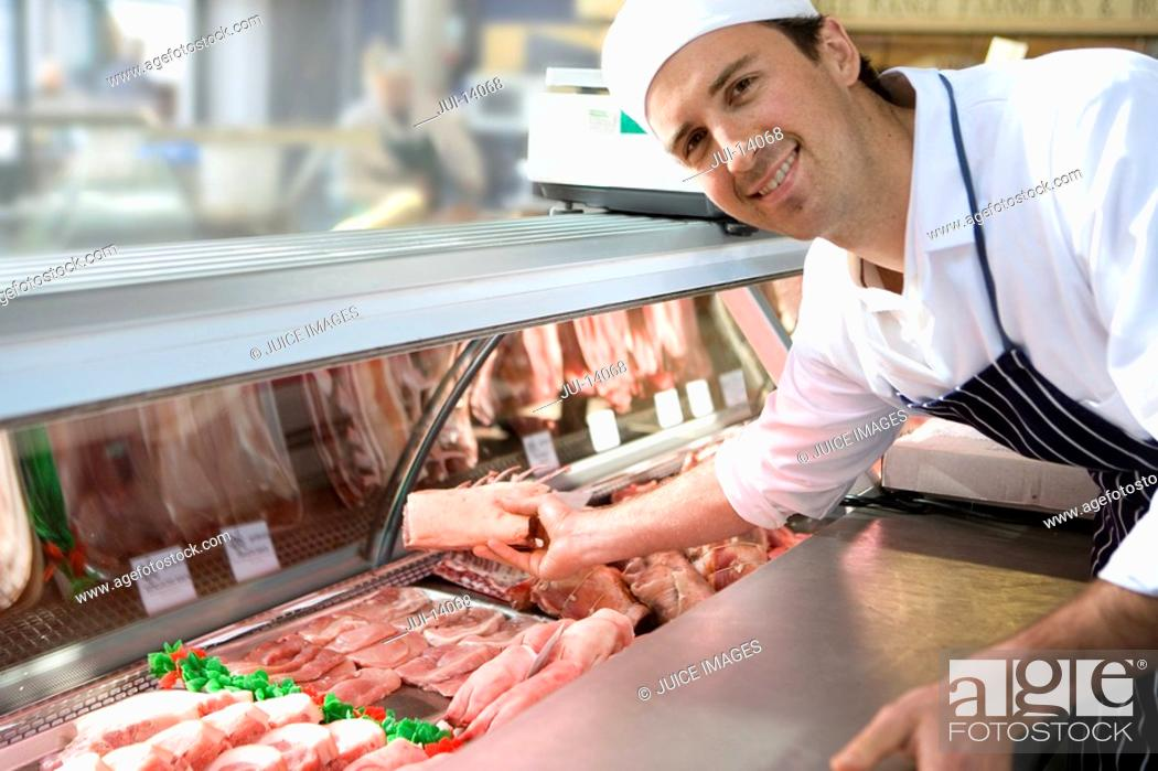 Stock Photo: Butcher reaching into display cabinet, smiling, portrait.