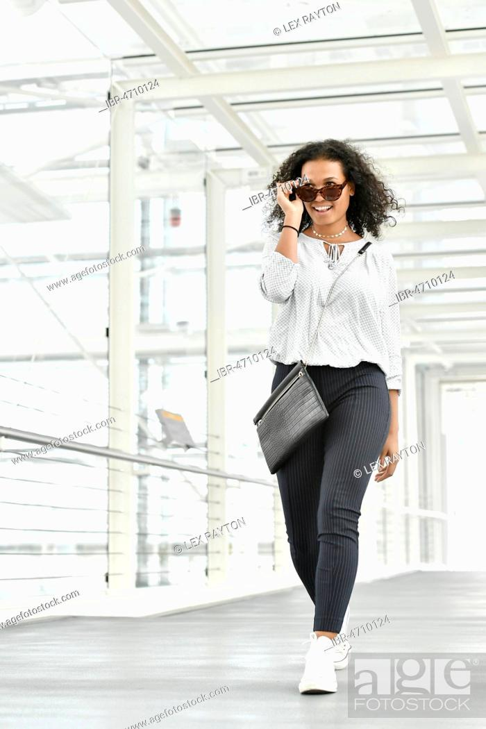 Stock Photo: Young woman, looks teasing, goes through glass tunnel, Germany.