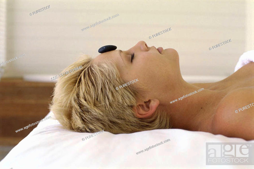 Stock Photo: Side profile of a young woman with a therapeutic stone on her forehead.