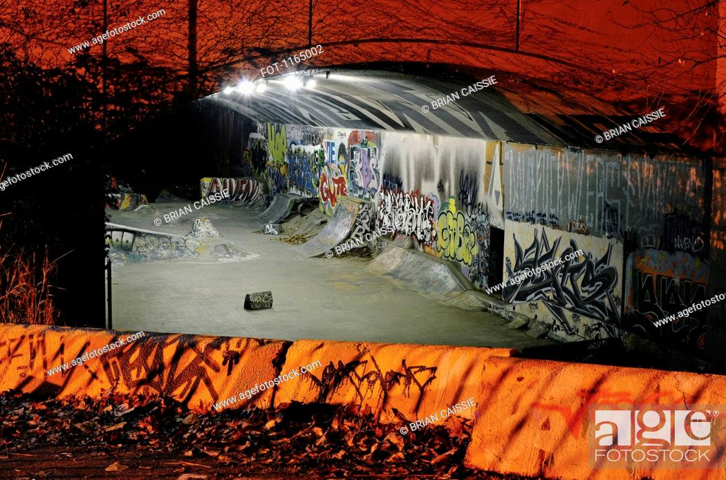 Stock Photo: Skateboarding ramps and graffiti in a tunnel at night.