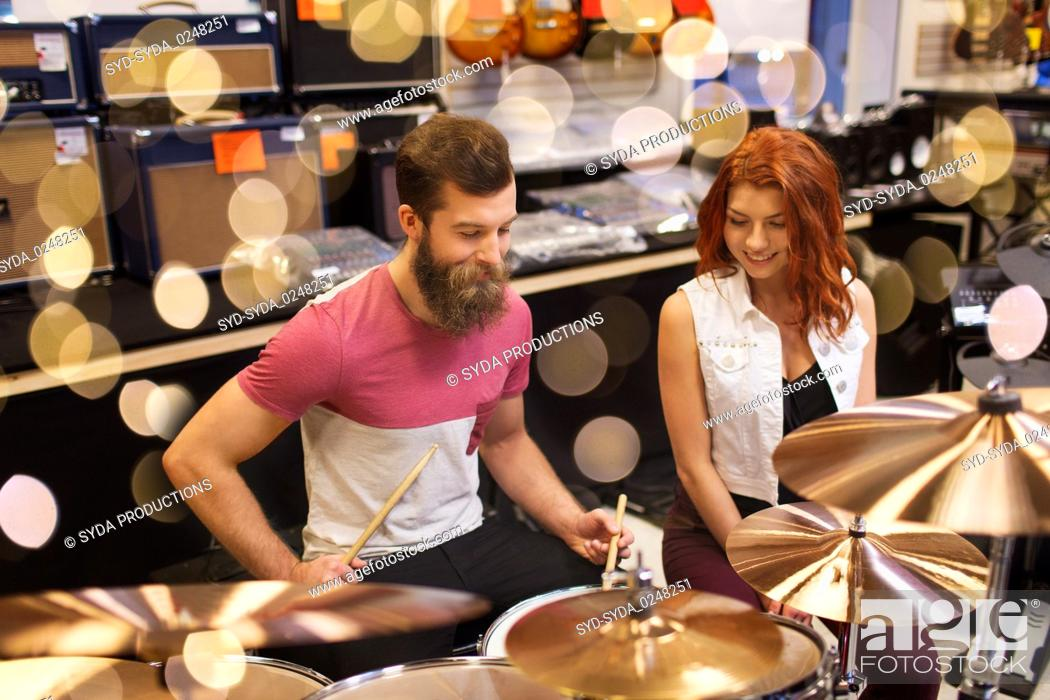 Imagen: happy man and woman playing cymbals at music store.