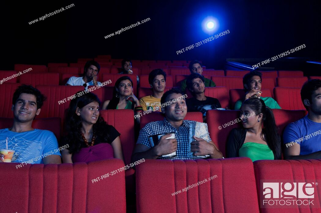Stock Photo: Youngsters enjoying movie in a cinema hall.