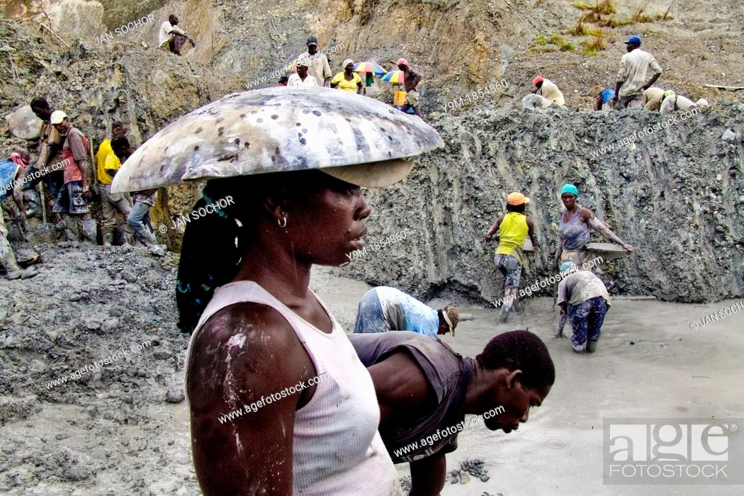 Hundreds of women gold miners digg the goldbearing mud in the open on