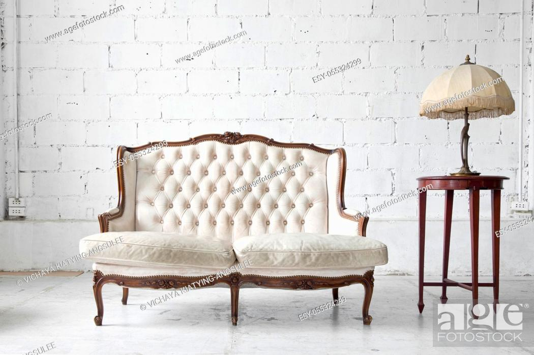 Stock Photo: White genuine leather classical style sofa in vintage room with desk lamp.