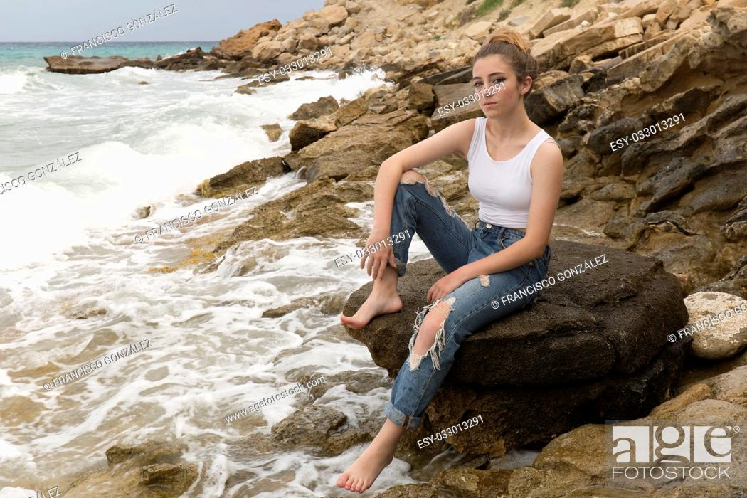 Photo de stock: Teenage girl sitting on the rocks of a creek of Villajoyosa, in the province of Alicante, Spain.