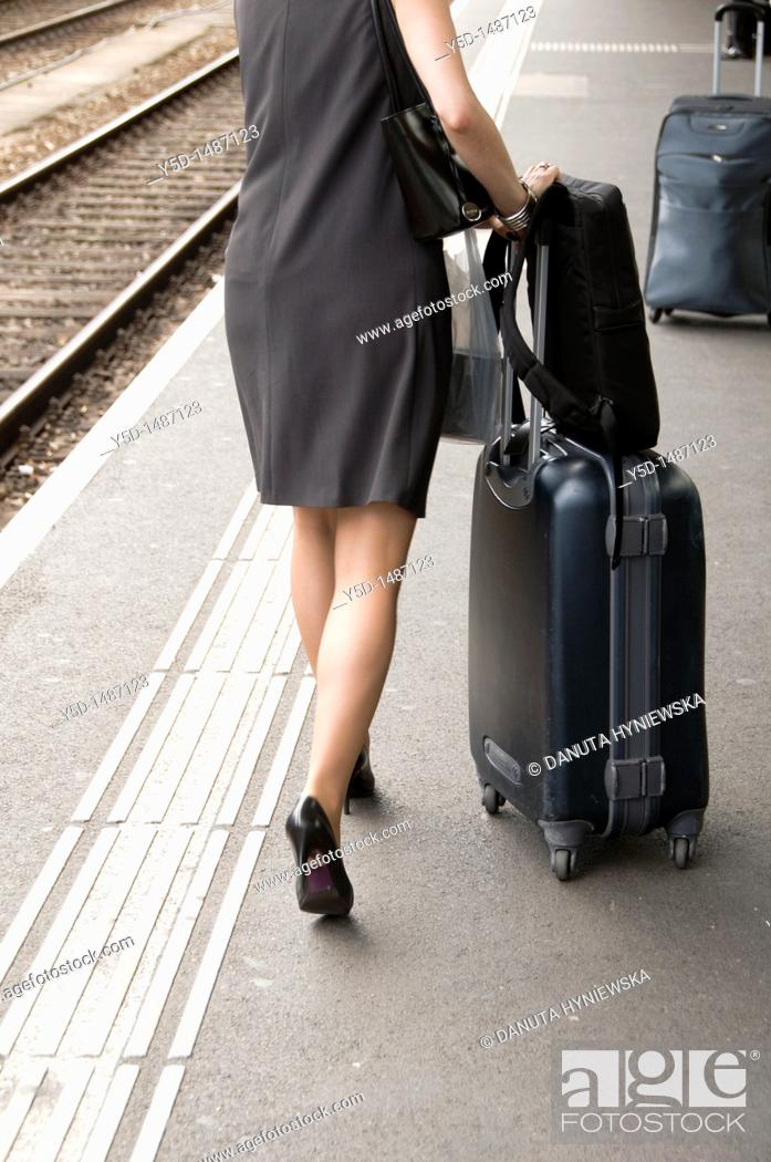 Stock Photo: travelling woman with suitcase and bags, high heel, dress, main train station, Geneva, Switzerland.