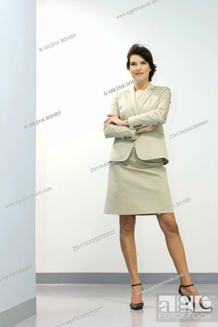 Stock Photo: Businesswoman standing with arms folded, smiling, looking away.