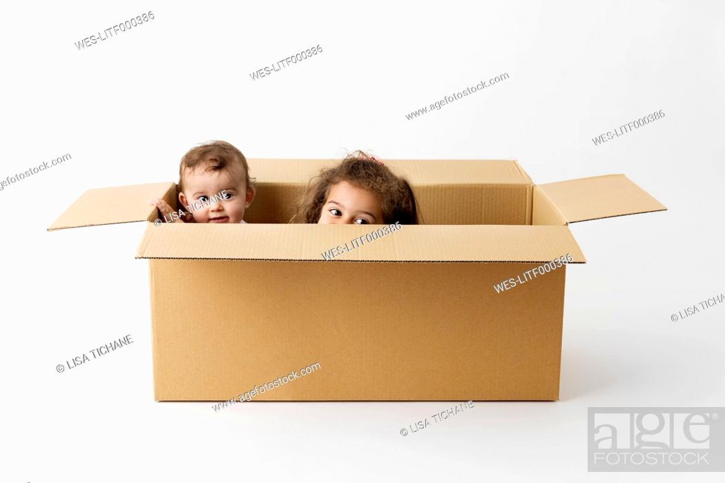 Stock Photo: Two little children hiding together in a cardboard box.