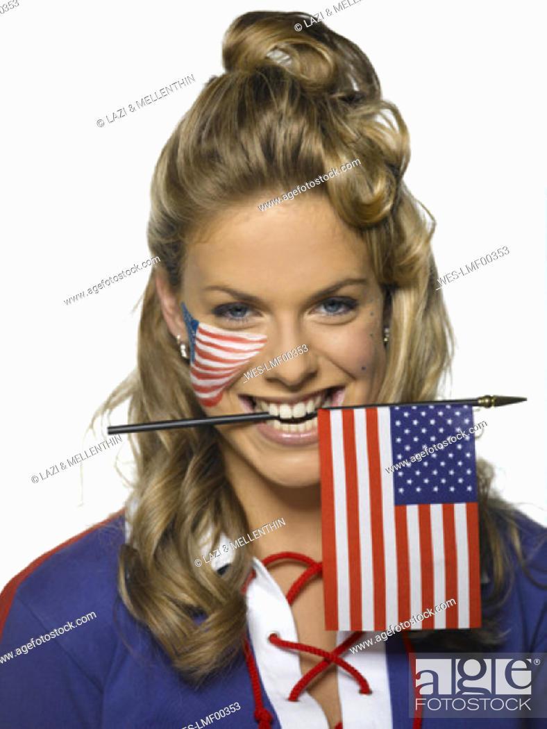 Imagen: Young woman holding US flag between teeth, portrait.