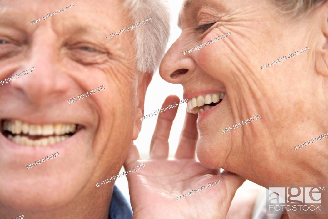 Stock Photo: Spain, Senior woman whispering into ear of man, smiling.