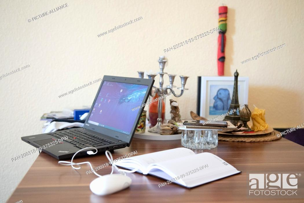 Stock Photo: 18 March 2020, Saxony, Dresden: Due to the spread of the coronavirus in a living room, a laptop stands on the dining table next to a calendar.