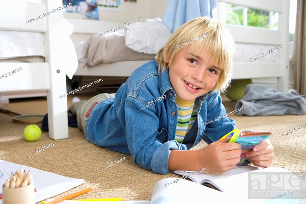 Stock Photo: Boy 6-8 with packet of marker pens in bedroom, smiling, portrait.