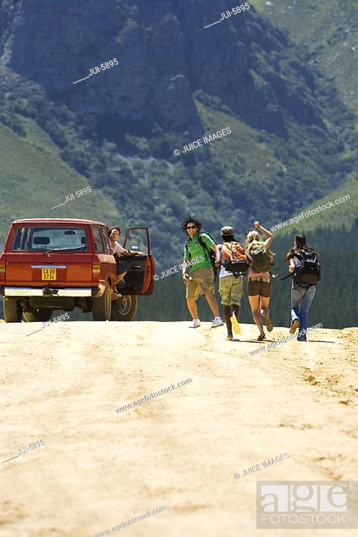 Stock Photo: Four young adults, with rucksacks, running up to stationary jeep on dirt track in mountain valley, rear view.