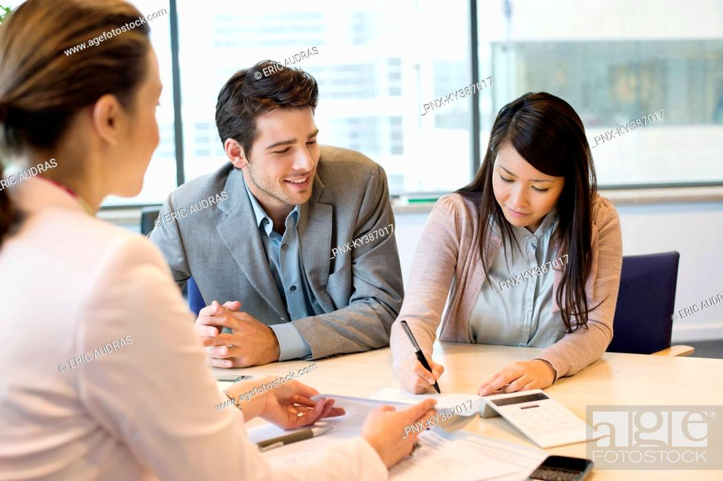 Stock Photo: Couple signing documents with real estate agent.