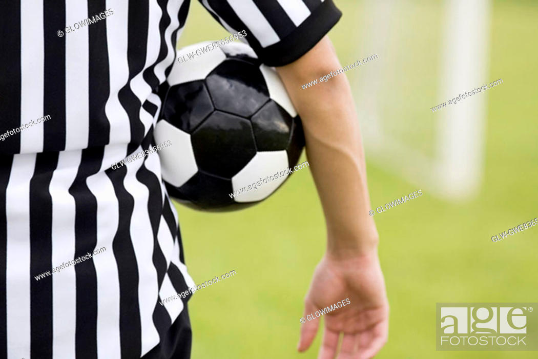 Stock Photo: Mid section view of a referee with a soccer ball under his arm.